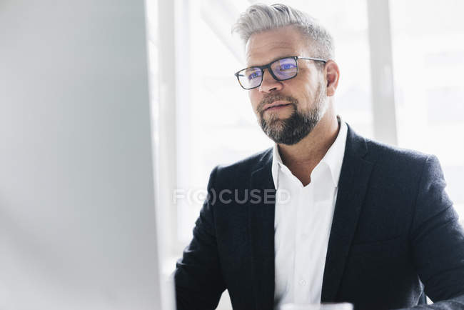 Businessman in suit standing in office — Stock Photo