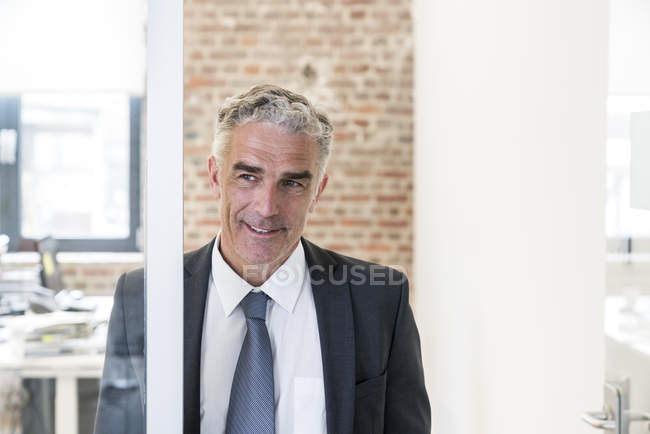 Businessman standing in modern office — Stock Photo