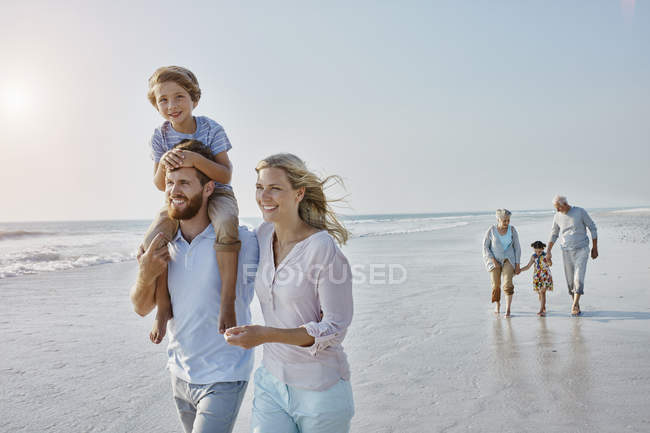 Extended family strolling on beach — Stock Photo