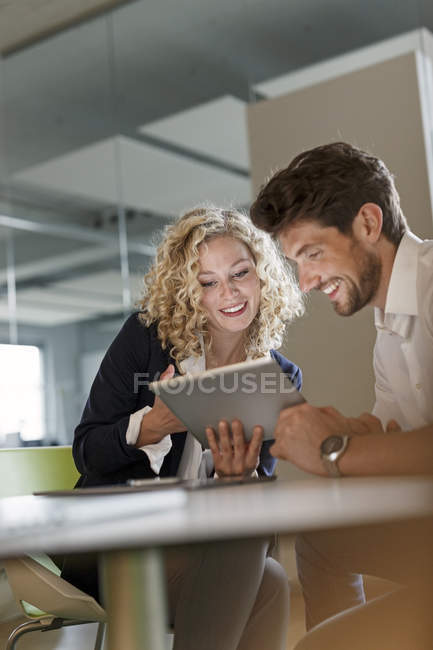 Colleagues sharing tablet in office — Stock Photo