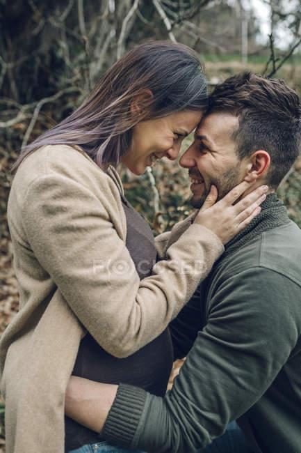 Mann mit lächelnden schwangere Frau umarmt — Stockfoto