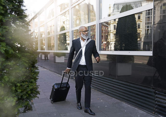 Businessman walking by street with suitcase — Stock Photo