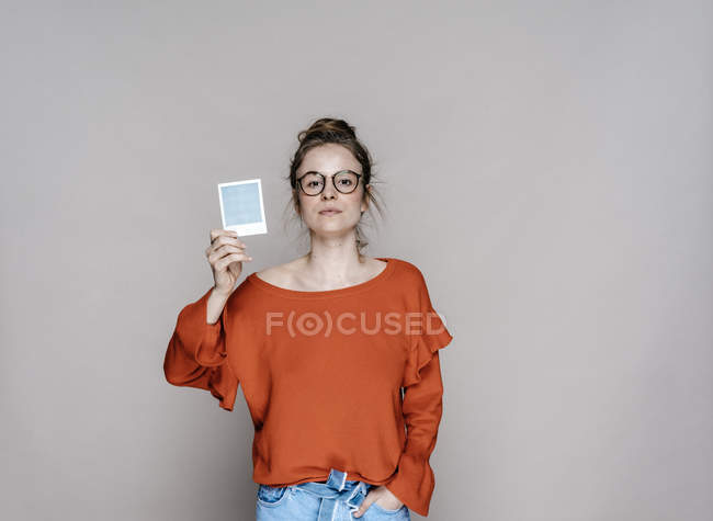 Woman holding instant photo — Stock Photo