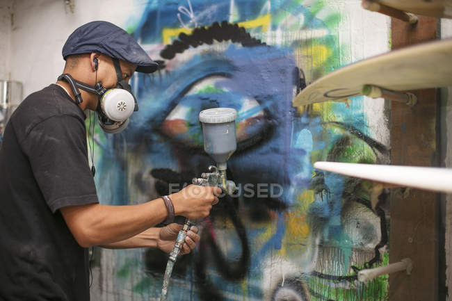 Surfshop employee spray painting — Stock Photo