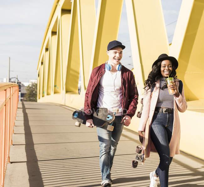 Coppia con skateboard passeggiando sul ponte — Foto stock