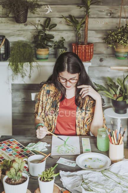 Mulher pintando plantas com aquarelas — Fotografia de Stock