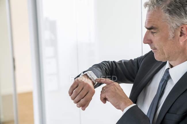 Homme d'affaires vérifiant l'heure avec montre — Photo de stock