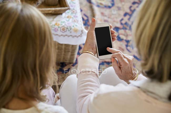 Бабушка сидит рядом с внучкой, используя смартфон — стоковое фото