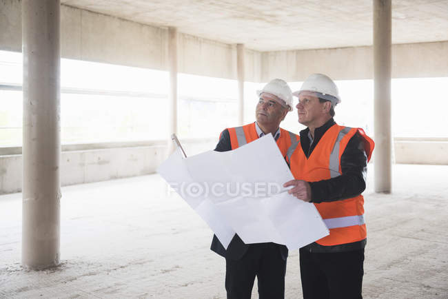 Men with plan wearing safety vests — Stock Photo