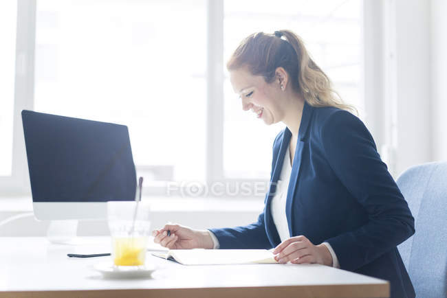 Businesswoman working at desk in her office — Stock Photo