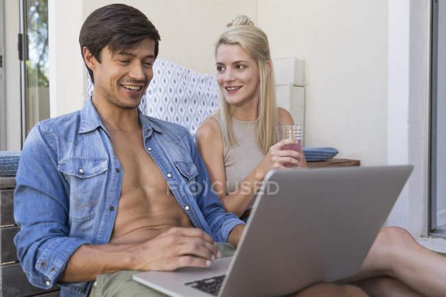 Uomo e donna che utilizzano il computer portatile sulla terrazza — Foto stock