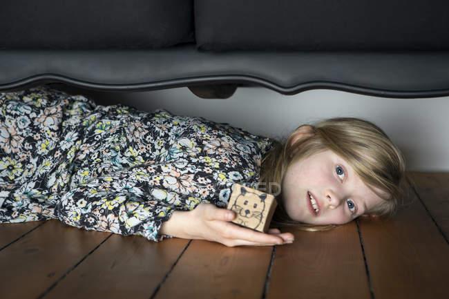 Girl lying on floor and holding box — Stock Photo