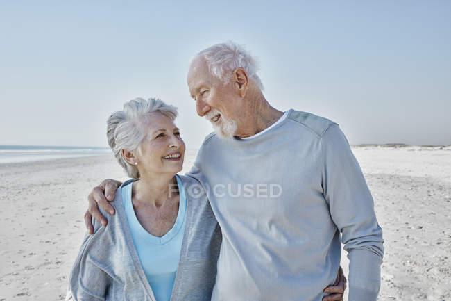 Улыбающаяся пожилая пара на пляже — стоковое фото