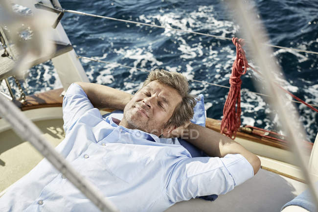 Uomo maturo sdraiato sul ponte — Foto stock