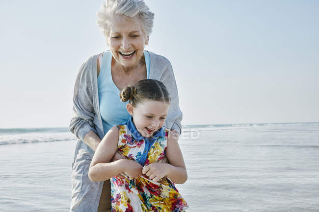 Grandmother with granddaughter on beach — Stock Photo