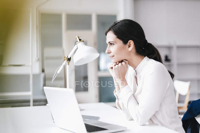 Donna d'affari con computer portatile a tavola pensando — Foto stock