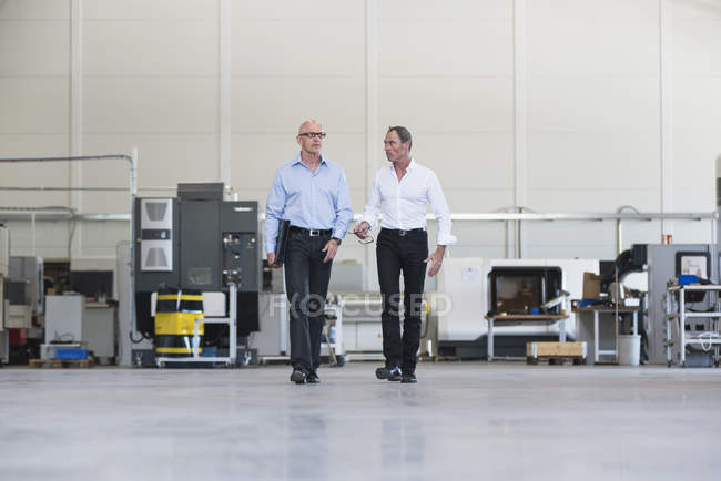 Businessmen walking and talking in factory — Stock Photo