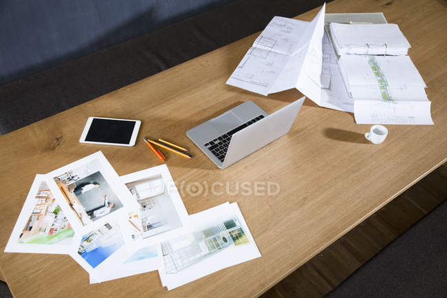 Desk with laptop photographies and blueprint — Stock Photo