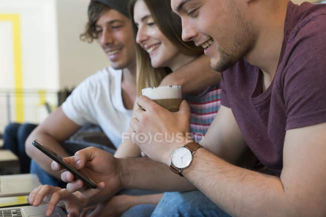 Amigos usando telefone celular e computador portátil — Fotografia de Stock