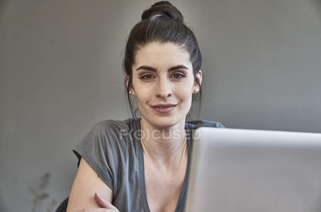 Femme assise avec ordinateur portable — Photo de stock