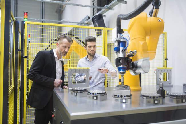 Бізнесмени, спостерігаючи Промисловий робот — стокове фото