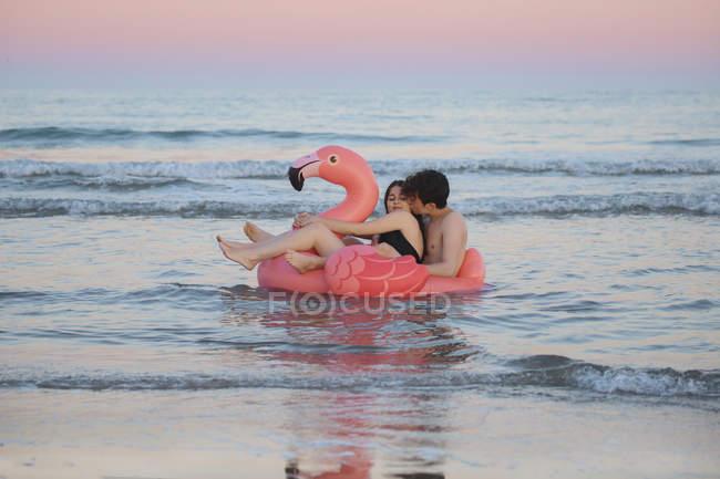 Casal flutuante com flamingo rosa inflável — Fotografia de Stock