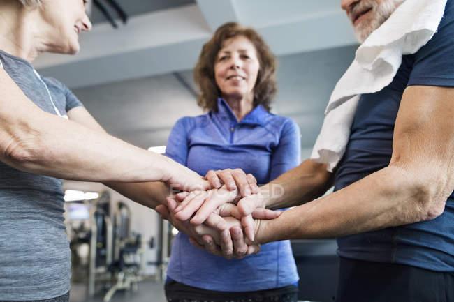 Пожилые люди укладывают руки в тренажерный зал — стоковое фото