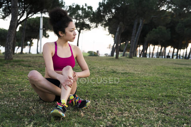 Young jogger having a rest on a meadow — Stock Photo