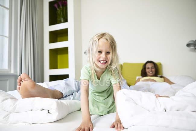 Menina com os pais, deitada na cama — Fotografia de Stock