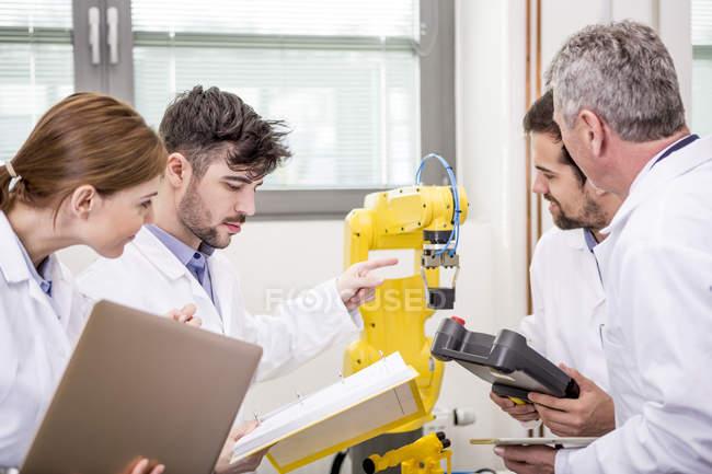 Engineers examining industrial robot — Stock Photo