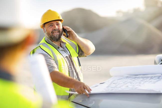 Trabajador de cantera hablando por teléfono - foto de stock