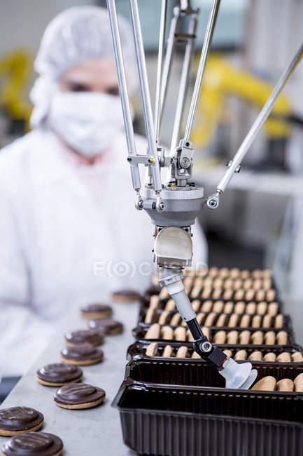 Женщина на заводе рассматривает печенье робота — стоковое фото