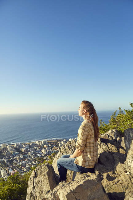 Woman sitting on rock with view to city — Stock Photo