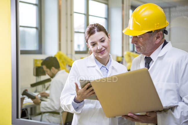 Two engineers in factory with tablet and laptop — Stock Photo