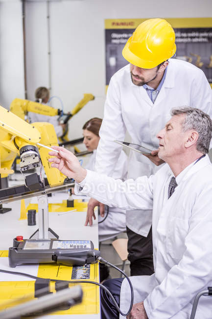 Two engineers examining industrial robot — Stock Photo