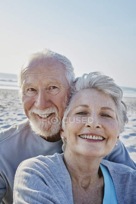 Smiling senior couple on beach — Stock Photo