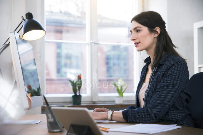 Woman working on computer at desk — Stock Photo