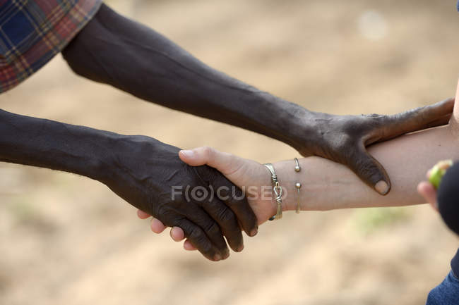 Burkina Faso, old African man shaking hands with white woman — Stock Photo