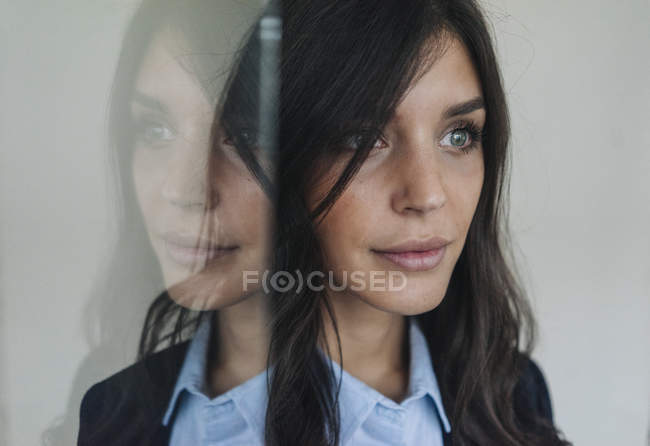 Woman reflected in glass pane — Stock Photo