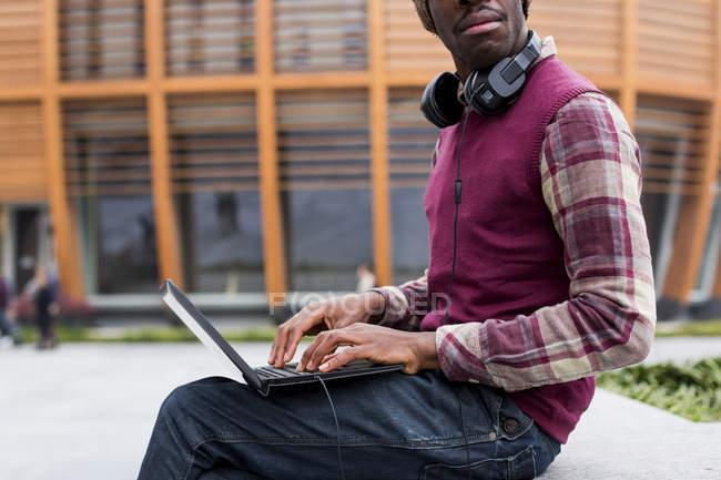 Uomo con cuffie utilizzando laptop — Foto stock