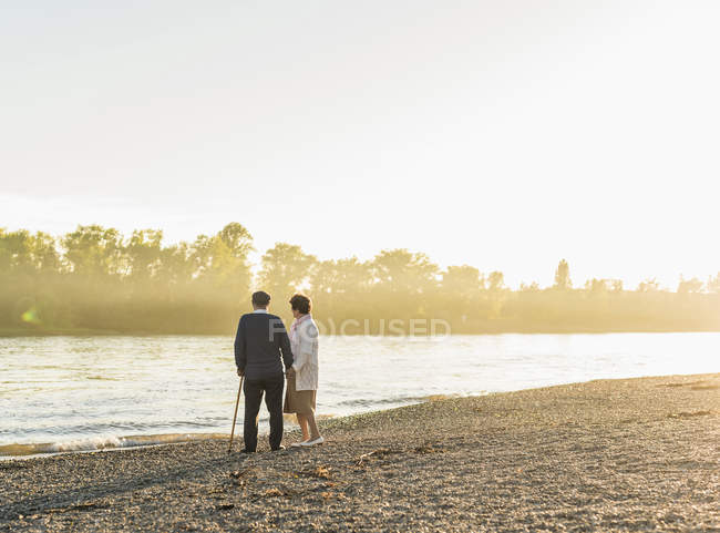 Senior couple standing on at riverside — Stock Photo
