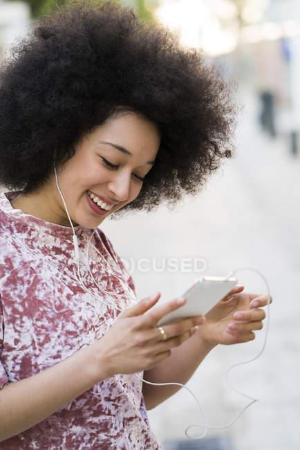 Mulher com fones de ouvido olhando para o celular — Fotografia de Stock