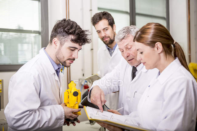 Engineers with industrial robot model checking documents — Stock Photo