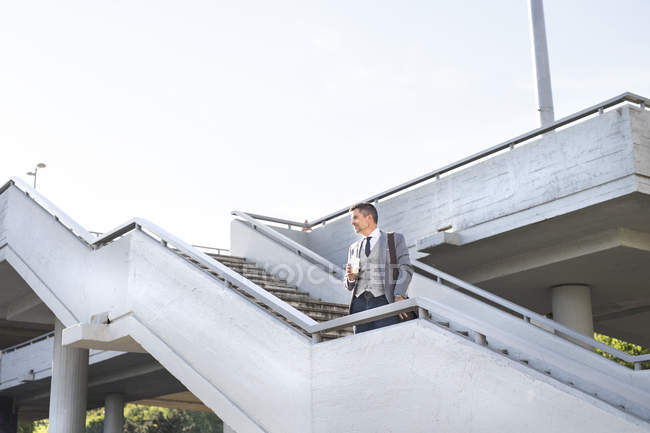 Businessman standing on stairs with takeaway coffee — Stock Photo