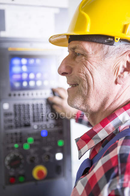 Worker operating high speed milling machine — Stock Photo