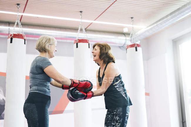 Senior women with boxing gloves in gym — Stock Photo