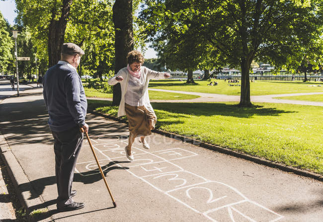 Senior woman playing hopscotch — Stock Photo