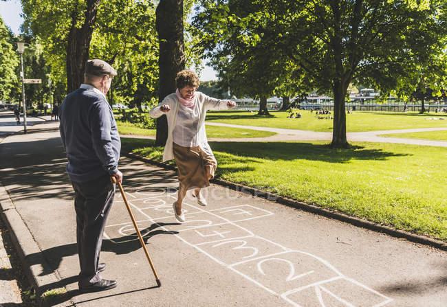 Donna anziana giocare hopscotch — Foto stock