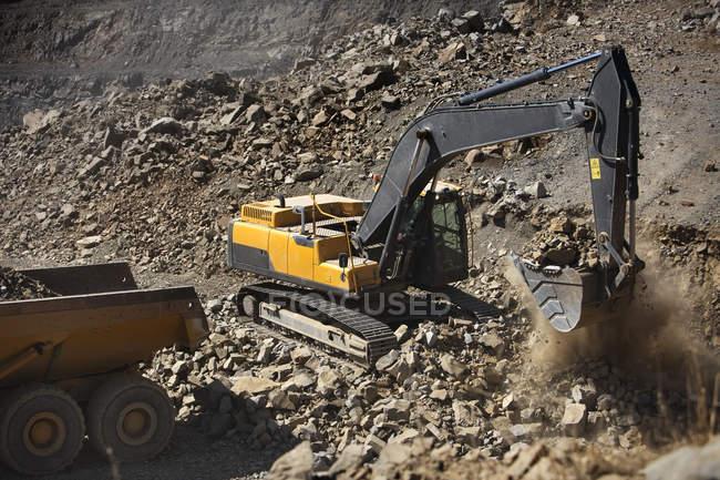 Gelber Bagger gräbt Erde aus — Stockfoto