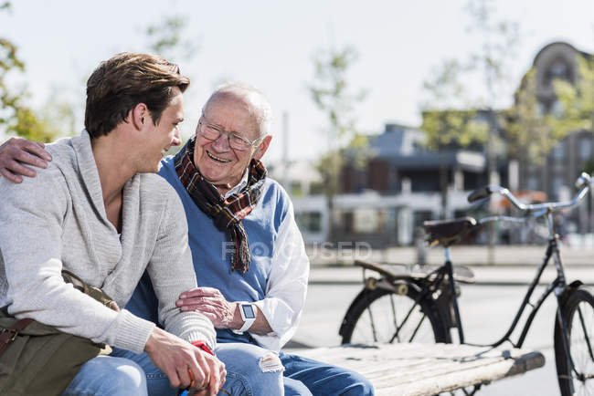 Man with adult grandson sitting on bench — Stock Photo